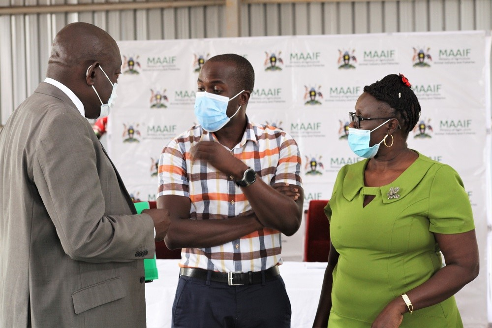 Three attendees of the Uganda launch of the BioProtection portal stand to discuss. From left to right: Mr. Paul Mwambu, Commissioner Crop Inspection and Certification, Senior Inspector, Mr. Fred Muzira, and Christine Alokit, Communication and Extension Scientist at CABI stand in a group wearing face masks.